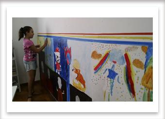 Crianças fazendo pintura mural.